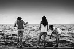 Barn som spelar på sjösidan Arkivfoton