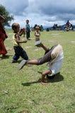 Barn som spelar på skolafältet som arbetar på huvudståenderna Arkivbilder