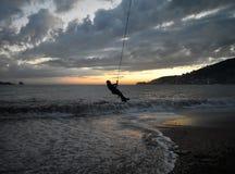 Barn som spelar på solnedgången vid havet royaltyfria bilder