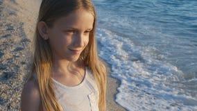 Barn som spelar på stranden i solnedgång, hållande ögonen på havsvågor för unge, flickastående på kust royaltyfri fotografi