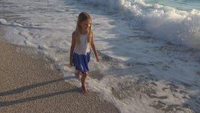 Barn som spelar på stranden på solnedgången, lycklig unge som går i havsvågflicka på sjösidan fotografering för bildbyråer