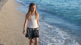 Barn som spelar på stranden på solnedgången, lycklig unge som går i havsvågflicka på sjösidan arkivfilmer
