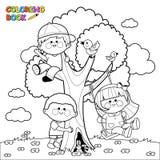Barn som spelar på en sida för trädfärgläggningbok Arkivbild
