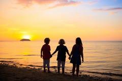 Barn som spelar p? havstranden Unge p? solnedg?nghavet royaltyfria foton