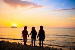 Barn som spelar p? havstranden Unge p? solnedg?nghavet arkivbild