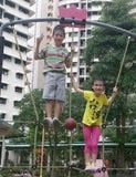 Barn som spelar på lekplatsen Arkivbild