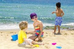 Barn som spelar på stranden Arkivbild
