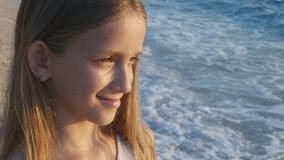 Barn som spelar p? stranden i solnedg?ng, h?llande ?gonen p? havsv?gor f?r unge, flickasikt p? solnedg?ngen arkivfilmer