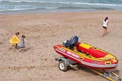 Barn som spelar på stranden nära ett bränningräddningsaktionfartyg i Umhlanga, vaggar Arkivbild