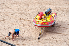 Barn som spelar på stranden nära ett bränningräddningsaktionfartyg i Umhlanga, vaggar Royaltyfria Foton