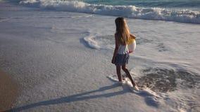 Barn som spelar p? stranden p? solnedg?ngen, lycklig unge som g?r i havsv?gflicka p? sj?sidan lager videofilmer