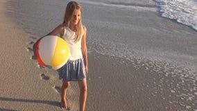 Barn som spelar p? stranden p? solnedg?ngen, lycklig unge som g?r i havsv?gflicka p? sj?sidan arkivfilmer