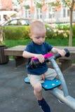 Barn som spelar p? utomhus- lekplats i sommar Ungar spelar p? dagisg?rd Aktiv unge som rymmer gunga och en rosa skopa arkivfoto