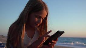 Barn som spelar Smartphone, unge på stranden på solnedgången, flicka som använder minnestavlan på kusten lager videofilmer