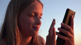 Barn som spelar Smartphone, unge p? stranden p? solnedg?ngen, flicka som anv?nder minnestavlan p? kusten arkivfilmer