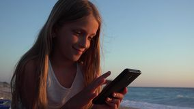 Barn som spelar Smartphone, unge p? stranden p? solnedg?ngen, flicka som anv?nder minnestavlan p? kusten lager videofilmer