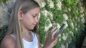 Barn som spelar Smartphone vid stenväggen i gården, flickabruk minnestavla, utomhus- unge stock video