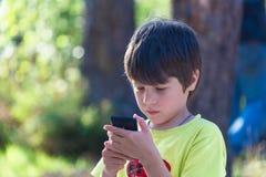 Barn som spelar telefonen utomhus Fotografering för Bildbyråer