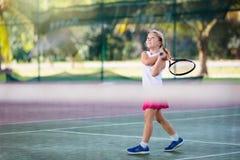 Barn som spelar tennis p? den utomhus- domstolen arkivbilder