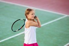 Barn som spelar tennis p? den utomhus- domstolen royaltyfri foto
