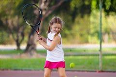 Barn som spelar tennis p? den utomhus- domstolen arkivbild