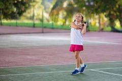 Barn som spelar tennis p? den utomhus- domstolen arkivfoton