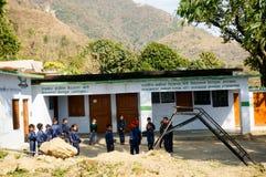 Barn som spelar utanför en byskola Arkivfoto