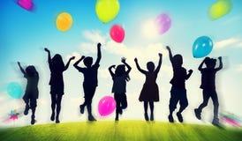 Barn som spelar utomhus ballongsamhörighetskänslabegrepp Arkivfoto