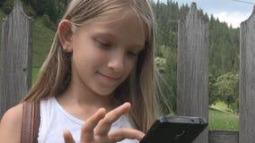 Barn som spelar utomhus- Smartphone, unge som bl?ddrar minnestavlan, flicka som kopplar av i natur lager videofilmer