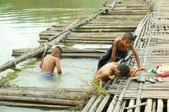 Barn som spelar vatten i floden Arkivfoton