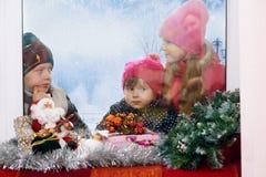 Barn som står utanför fönstret på en vinterdag som ut ser fönstret på vintergåvorna Royaltyfri Foto