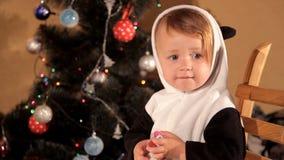 Barn som svänger i en fåtölj nära en julgran stock video