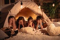 Barn som täcker framsidan med händer, medan vila i tält hemma royaltyfria bilder