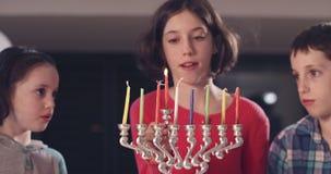 Barn som tänder Chanukkahstearinljus hemma