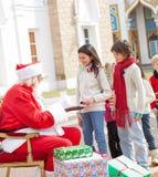 Barn som tar kex från Santa Claus Royaltyfria Bilder