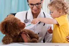 Barn som tar temperatur av nallebjörnen Royaltyfria Foton