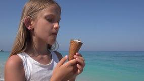 Barn som ?ter glass p? stranden p? solnedg?ngen, liten flicka p? kusten i sommar arkivfilmer