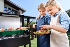Barn som testar nytt kött som precis utomhus lagas mat på grillfestgaller Royaltyfri Foto