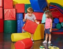 Barn som tillsammans spelar i idrottshall arkivfoto