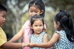 Barn som tillsammans spelar i parkera Royaltyfria Bilder