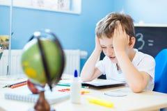 Barn som tänker om läxalösning Arkivbild
