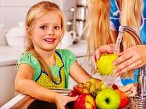Barn som tvättar frukt på kök Arkivbilder