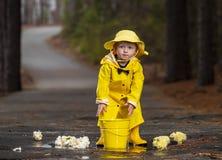 Barn som tycker om regnet i hans galoscher arkivbilder