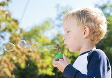 Barn som utanför gör såpbubblor arkivbilder