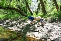 Barn som utanför spelar på floden arkivbild