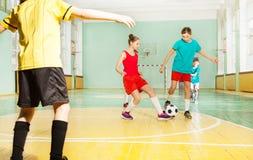 Barn som utbildar fotboll i skolagymnastiksal royaltyfri fotografi