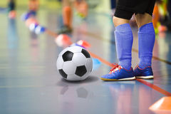 Barn som utbildar futsal inomhus idrottshall för fotboll Den unga pojken med fotboll klumpa ihop sig Royaltyfria Bilder