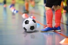 Barn som utbildar futsal inomhus idrottshall för fotboll Den unga pojken med fotboll klumpa ihop sig Arkivfoto