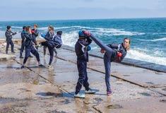Barn som utbildar karate på stenkusten Royaltyfria Foton