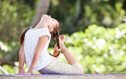 Barn som utomhus gör övning på plattformen Sund livsstil isolerad vit yoga för bakgrund flicka royaltyfri foto